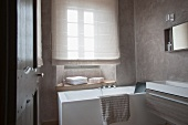 Designer bathroom - view through open door of bathtub below window with drawn blind and modern trough-style wash basin against wall