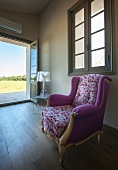 Rococo reading chair with colourful, spotted designer upholstery in minimalist room with traditional ambiance and view of landscape through open garden door