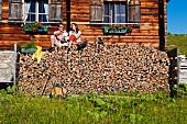 Paar sitzt auf einem Brennholzstapel bei einem Holzhaus
