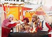 Old man serving punch at Christmas market