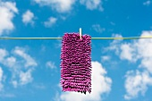 Mop hanging on washing line against blue sky