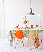 White room with cheerful accents of colour; dining area with various chairs and retro lamp