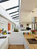 Designer kitchen with colourful wall tiles below skylight in modern, open-plan interior