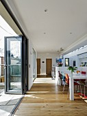 Dining table and colourful chairs on wooden floor in open-plan interior with folding glass door