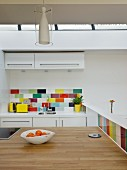 Kitchen counter with wooden worksurface in open-plan kitchen with colourful wall tiles