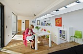 Woman holding baby on lap sitting at white dining table in contemporary, open-plan interior