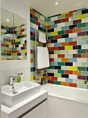 Bathroom with washstand and mirrored cabinet next to bathtub against wall with colourful tiles