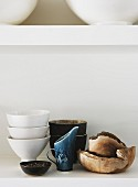 Various items of crockery made of china, ceramics and wood arranged on white shelf