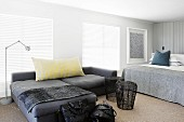 Dark grey chaise sofa and wire mesh side tables next to double bed in modern bedroom with closed louver blinds