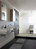 Two washbasins below mirrored cabinets and shower area with glass partition in modern bathroom