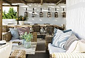 Rattan sofa set with seat cushions and scatter cushions under terrace pergola of holiday home