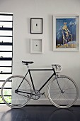 Racing bicycle on dark wooden floor below retro poster and miniature artworks