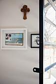 Wooden cross and framed pictures behind French window with horizontal glazing bars and metal frame