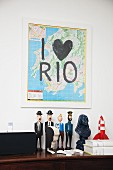 Map with lettering reading 'I love Rio' on wall above collection of comic character figurines