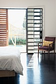 Retro chair in sunny bedroom with industrial-style French window and sliding wooden shutter