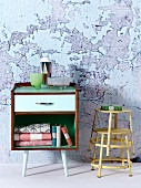 Small, fifties-style cabinet on legs next to stacked, yellow-painted metal stools against wall with crumbling plaster