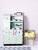 Fifties-style, pastel green kitchen dresser next to bag on chair against wallpaper with three-dimensional pattern