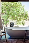 Free-standing designer bathtub in front of glass wall with view into sunny garden