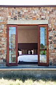 Open double terrace doors in stone facade with view into modern bedroom
