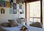 Single bed below posters pinned on wall with vintage bedside table and open louver blinds on balcony door to one side