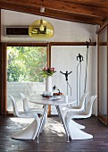 White, plastic shell chairs around table below pendant lamp with yellow, transparent lampshade in front of balcony door and metal sculptures