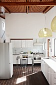 Pendant lamps with glass lampshades in white designer kitchen with dark terracotta floor