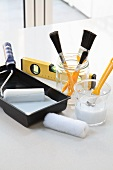 Painting utensils: paint, paintbrushes, rollers and spirit level