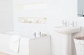 Pedestal washbasin and bathtub in white bathroom