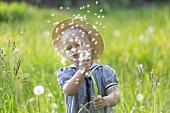 Blonde little girl blowing on a dandelion clock