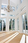 Light-flooded empty living room with terrace doors, wooden floor and chandelier