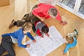 Family sitting on floor with plan of apartment