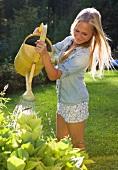 Blond teenager water plants in garden