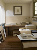 Black and white photographs on two tables in gallery study of historic country house