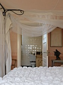 Bed with white bedspread and voile draped from canopy frame; bathroom in background
