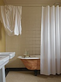 Free-standing bathtub painted with marbled effect behind white curtain in simple bathroom