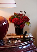 Autumnal bouquet, books, bead necklace and lamp on Baroque-style bedside table