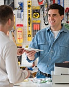 Hardware store sales clerk handing over purchase