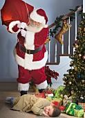 Santa Claus looking at boy sleeping next to Christmas tree