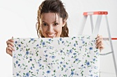 Smiling woman holding piece of wallpaper