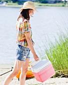 Frau mit Kühlbox am See