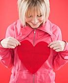 Blonde Frau hält ein Herz aus Filz