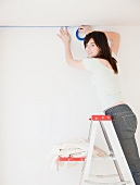 Portrait of young woman on ladder preparing to paint room