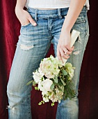 Woman in jeans holding bouquet of flowers
