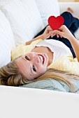 USA, New Jersey, Jersey City, Attractive young woman holding red heart