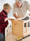 Grandfather and grandson (8-9) improving wooden stool