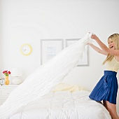 USA, New Jersey, Jersey City, young woman making bed