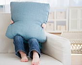 Girl (2-3) sitting on sofa hiding behind pillow