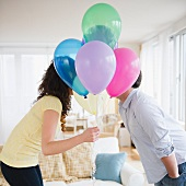 Couple kissing behind bunch of colorful balloons