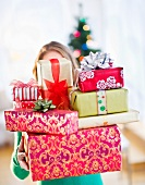 Young woman with stack of colorful Christmas gifts
