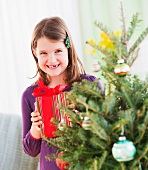 Girl (8-9) standing with gift behind Christmas tree